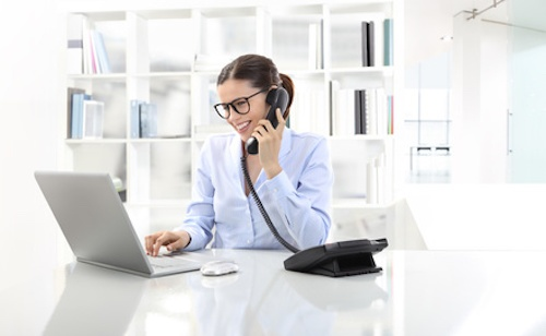 Smiling Woman In Office At Desk With Computer, Talking On The Phone